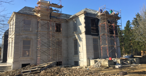 scaffolding on the side of a half built suburban mansion