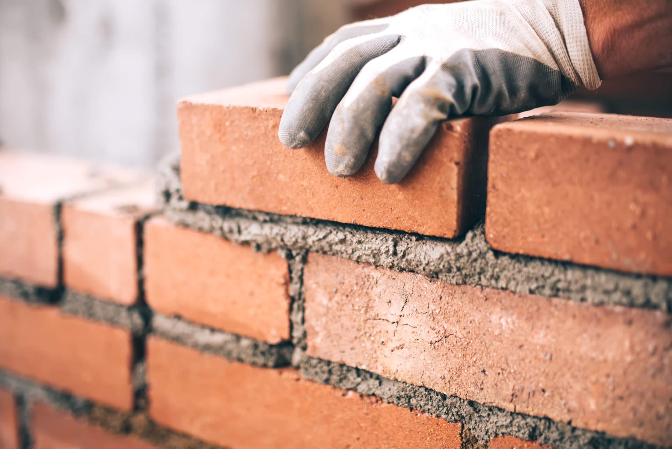 man laying down bricks